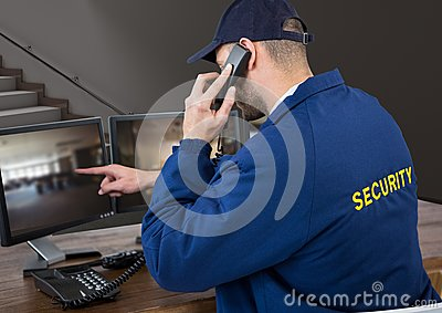 Security guard in his office phoning and pointing something in the screen