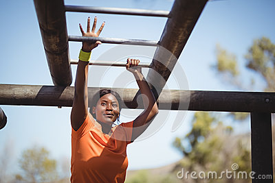 Determined woman exercising on monkey bar during obstacle course