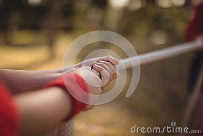 Hands of kid practicing tug of war during obstacle course