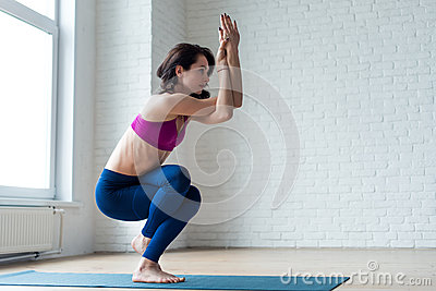 Thin girl in activewear doing yoga exercise Garudasana or Eagle pose with bare feet on mat in sports club