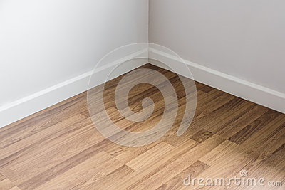 Laminated wood floor with white wall, room`s corner