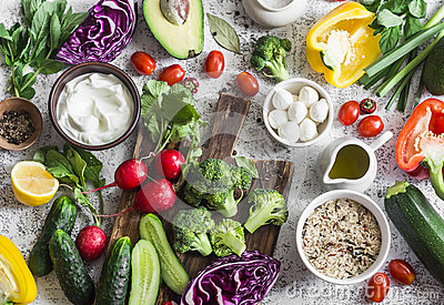stock image of balanced healthy diet food background in a mediterranean style. fresh vegetables, wild rice, fresh yogurt and goat cheese on a lig