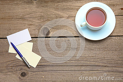 Blank business cards with pen and tea cup on wooden office table