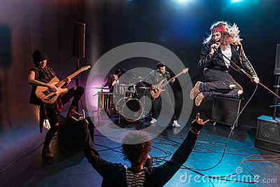 Back view of young woman gesturing rock and roll hand sign and looking at band