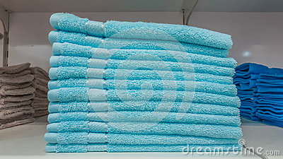 Fluffy bathing towels in blue and cyan colors stacked on shelf for sale in a store