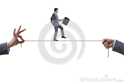 The businessman walking on tight rope in business concept
