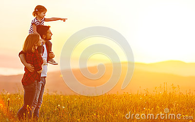 Happy family: mother father and child daughter on sunset