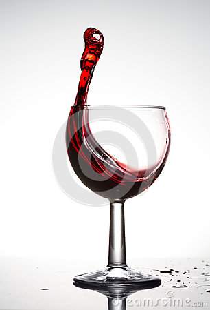 Pure wineglass with wave of brightly red wine on white background
