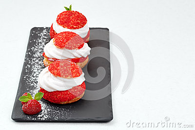 French Cakes with strawberry cream shanti. aery brewing cake on black shale. Restaurant composition on white background.
