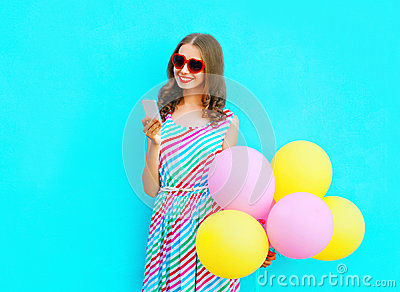 happy smiling woman using smartphone holding an air colorful balloons