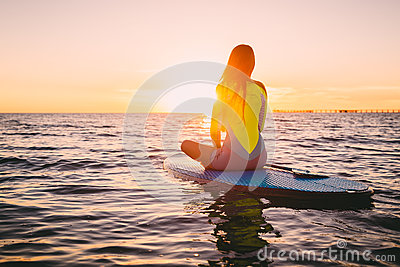 Stand up paddle boarding on a quiet sea with warm summer sunset colors. Relaxing on ocean
