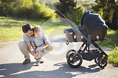 Father with little son and baby daughter in stroller. Sunny park.
