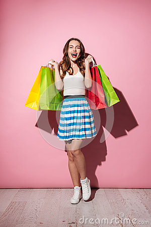 Happy excited woman shopaholic holding colorful shopping bags