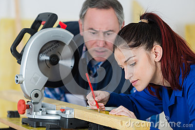 Young woman working at carpenter shop with teacher