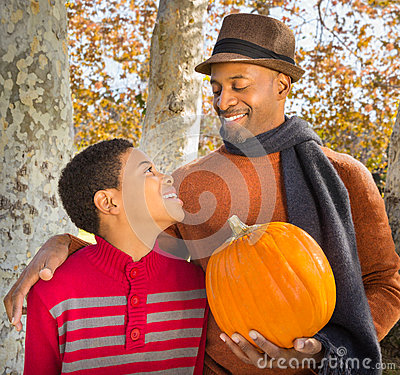 Portrait of Handsome African-American father and happy son choosing a pumpkin in Autumn.