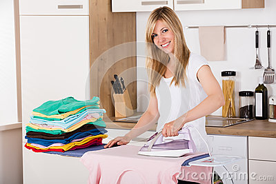 Smiling Woman Ironing Clothes With Electric Iron