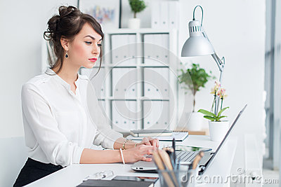 Young businesswoman working in office, typing, using computer. Concentrated woman searching information online