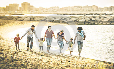 stock image of happy multiracial families running together at beach at sunset