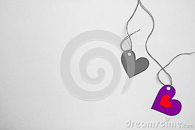 Two paper hearts tide to a string on a desaturate background