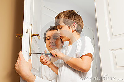 Young father helping his son to fix door-handle