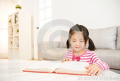 Clever girl at table with reading books