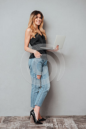 Portrait of a smiling pretty woman standing and holding laptop