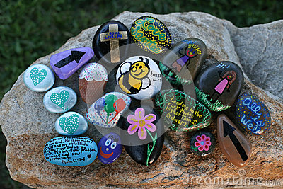 Many decorated painted rocks displayed on a small boulder