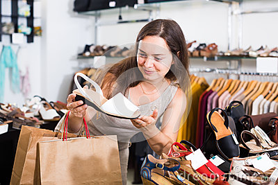 Friendly female customer selecting shoes in footgear center