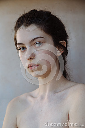 Beautiful Face of Young Girl with Clean Fresh Skin close up on grey background. Beauty Fine Art Portrait. Spa Woman