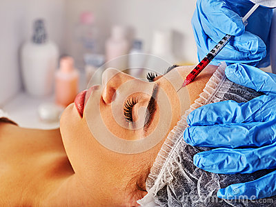 Filler injection for woman forehead face. Plastic aesthetic facial surgery .