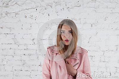 Cute young woman on leather jacket. Fashion model in pink leather jacket. Posing near white brick wall.