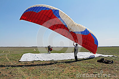 Assistant helps the paraglider to straighten the paraplane before the flight in Volgograd