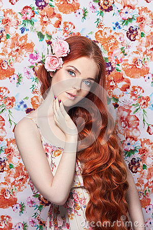 beautiful redhead girl with long hair. Perfect woman portrait with a colored light background. Gorgeous hair and deep eyes