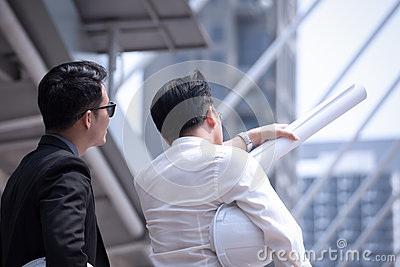 Asian businessman discuss with engineer architect in suite, look