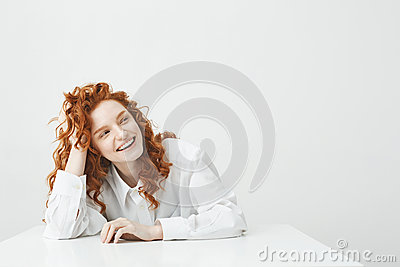 Cheerful pretty young girl with foxy hair smiling laughing sitting at table over white background.