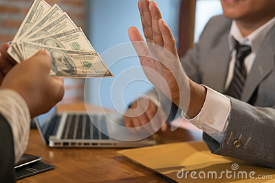 Businessman rejecting money cash banknote from a man. honest business people in suit refuse to take the bribe - anti bribery, cor