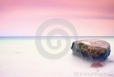 Romantic atmosphere in peaceful morning at sea. Big boulders sticking out from smooth wavy sea. Pink horizon