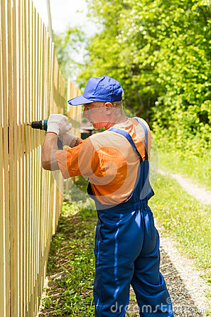 Close up portrait of skilled handyman mounting wooden board fence