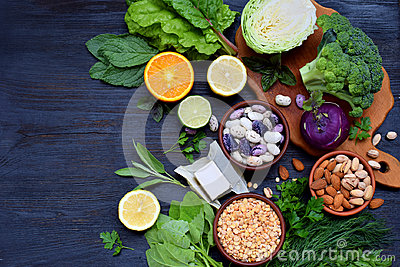 Composition on a dark background of products containing folic acid, vitamin B9 - green leafy vegetables, citrus, beans, peas, nuts