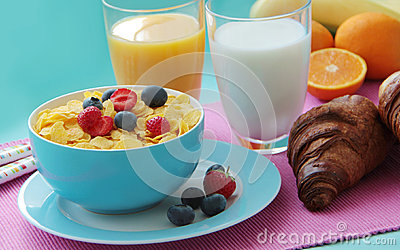 Breakfast with corn flakes, milk, croissants, orange juice and fresh fruits as banana, oranges and berries.