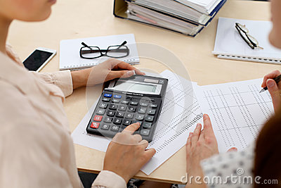 Two female accountants counting on calculator income for tax form completion hands closeup. Internal Revenue Service
