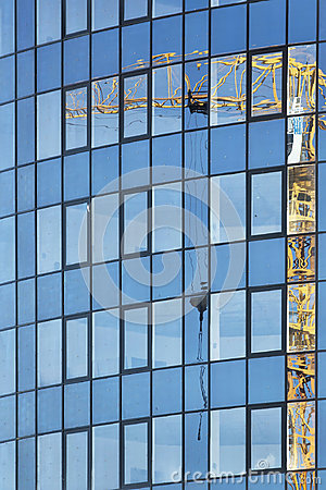 Reflection of construction crane on the glass of tall multistoried office building