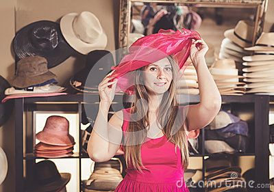 Adult nice woman try on pink boater hat in shopping mall