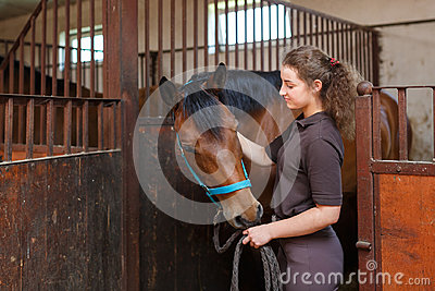 Girl with a horse in a stable