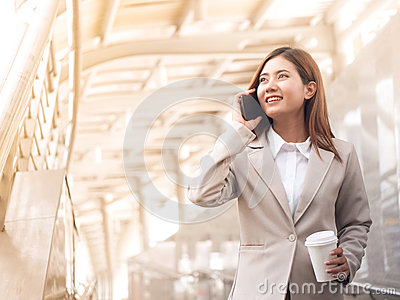 Smart asian business woman in a suit with mobile phone.