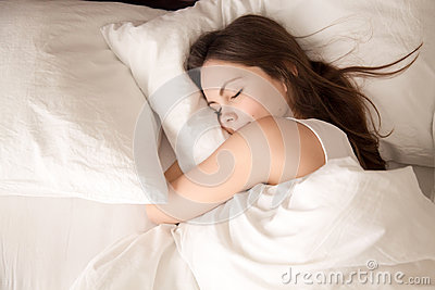 Woman sleeping in bed hugging soft white pillow