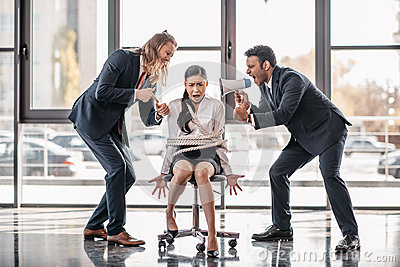 Asian businesswoman bound with rope on chair while businessmen screaming on her with megaphone