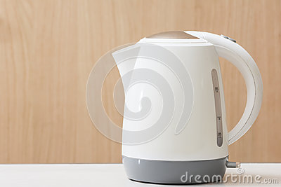 White Electric kettle quick boil on table and wooden background.