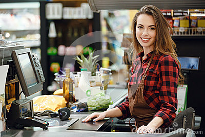Cashier lady on workspace in supermarket shop