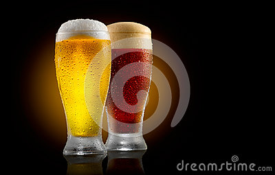 Craft beer. Two glasses of cold light and dark beer isolated on black